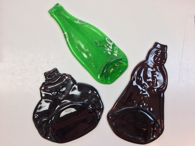 A glass bottle melted down to a flat plate